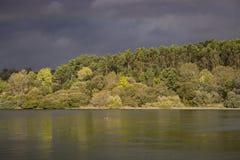 Donkerblauwe stormachtige hemel over rivier en bosaard vóór onweer Mooi rivierlandschap Meteorologie en weerconcept royalty-vrije stock afbeelding
