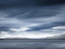 Donkerblauwe stormachtige wolken over de kustrotsen stock foto's