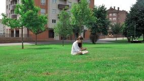 donkerbruin bruin het haarmeisje van 4 k vrij in witte blouse, gele borrels en zonnebril, die op het groene gras bij zitten stock footage