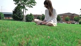 donkerbruin bruin het haarmeisje van 4 k vrij in witte blouse, gele borrels en zonnebril, die op het groene gras bij zitten stock video