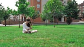 donkerbruin bruin het haarmeisje van 4 k vrij in witte blouse, gele borrels en zonnebril, die op het groene gras bij zitten stock videobeelden