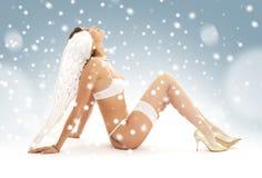 Donkerbruin engelenmeisje die in witte lingerie omhoog kijken Stock Foto