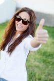 Donkerbruin koel meisje die met zonnebril O.k. zeggen Stock Foto