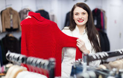 Donkerbruin langharig meisje die sweater kiezen stock afbeeldingen