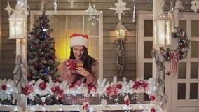 Donkerbruin meisje in de hoed die van de Kerstman groet verzenden die sms smartphone met behulp van een portiek stock video