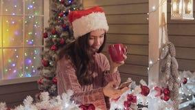 Donkerbruin meisje in de hoed die van de Kerstman groet verzenden die sms smartphone met behulp van een portiek stock footage
