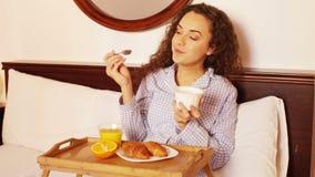 Donkerbruin meisje die gezond ontbijt in bed hebben thuis stock videobeelden