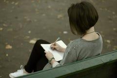 Donkerbruin meisje die op de park bank en het schrijven nota's in haar blocnote situeren Stock Foto's