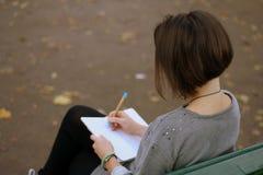 Donkerbruin meisje die op de park bank en het schrijven nota's in haar blocnote situeren Foto van erachter Royalty-vrije Stock Foto's