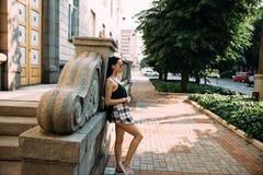 Donkerbruin meisje in een de zomerdag in de stad die om zonnebril dragen stock afbeelding