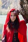 Donkerbruin meisje in een rode regenjas stock foto's