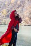 Donkerbruin meisje in een rode regenjas royalty-vrije stock afbeelding
