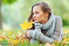Donkerbruin meisje en gouden bladeren Stock Foto's