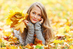 Donkerbruin meisje en gouden bladeren Royalty-vrije Stock Foto's