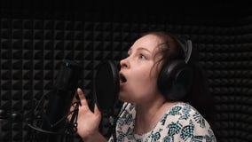 Donkerbruin meisje het emotionele zingen aan microfoon in vocale studio De begaafde jonge vrouwelijke kunstenaar registreert lied stock video