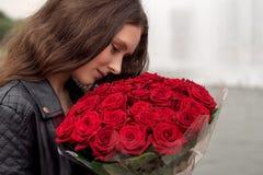 Donkerbruin meisje met een boeket van rode rozen stock afbeelding