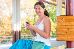 Donkerbruin meisje met een telefoon bij de post Stock Afbeeldingen