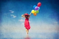 Donkerbruin meisje met kleurenballons bij kust. Royalty-vrije Stock Afbeelding
