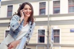 Donkerbruin meisje met lang haar die bij telefoon en het glimlachen spreken Royalty-vrije Stock Foto