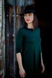 Donkerbruin meisje in zwarte met een modieuze hoed en een oude houten deur stock fotografie