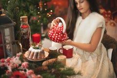 Donkerbruin meisjes gietende thee op de Kerstmislijst Stock Afbeelding