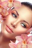 Donkerbruin modelmeisjesportret met orchideebloemen stock foto