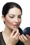Donkerbruin wijfje dat lippenstift in spiegel toepast Stock Foto's