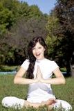 Donkerbruin yogameisje op groen gras in park. stock foto