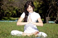 Donkerbruin yogameisje op groen gras in park. royalty-vrije stock foto's