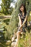 Donkerbruine Aziatische meisjeszitting bij de oever van het meer. Stock Foto