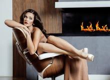 Donkerbruine de vrouwenzitting van schoonheidsyong dichtbij open haard Stock Foto's