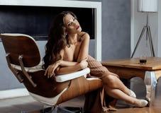 Donkerbruine de vrouwenzitting van schoonheidsyong dichtbij open haard Royalty-vrije Stock Afbeeldingen
