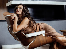 Donkerbruine de vrouwenzitting van schoonheidsyong dichtbij open haard Royalty-vrije Stock Foto's