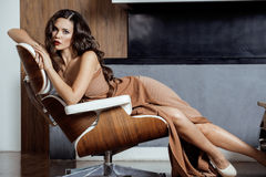 Donkerbruine de vrouwenzitting van schoonheidsyong dichtbij open haard Stock Afbeelding