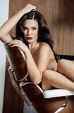Donkerbruine de vrouwenzitting van schoonheidsyong dichtbij open haard Stock Fotografie