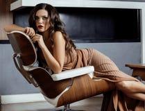 Donkerbruine de vrouwenzitting van schoonheidsyong dichtbij open haard Stock Afbeeldingen