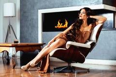 Donkerbruine de vrouwenzitting van schoonheidsyong dichtbij open haard thuis stock afbeelding
