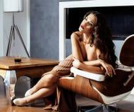 Donkerbruine de vrouwenzitting van schoonheidsyong dichtbij open haard thuis, de winter warme avond in binnenland stock foto's