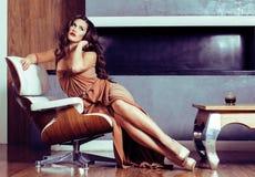 Donkerbruine de vrouwenzitting van schoonheidsyong dichtbij open haard thuis, winte stock foto's