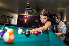 donkerbruine die vrouw op biljartspel wordt geconcentreerd royalty-vrije stock afbeelding