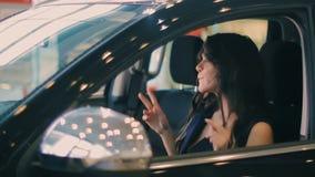 Donkerbruine en Vrouw die terwijl het zitten in auto dansen glimlachen stock footage