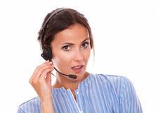 Donkerbruine exploitantdame die op hoofdtelefoons spreken Stock Afbeelding