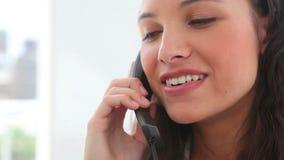 Donkerbruine haired vrouw die op de telefoon spreken Stock Afbeelding