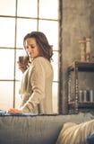 Donkerbruine holdingskop van koffie in zolder Stock Foto