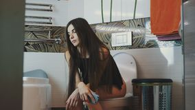 Donkerbruine jonge meisjeszitting op toilet met smartphone in handen Badkamers stock video
