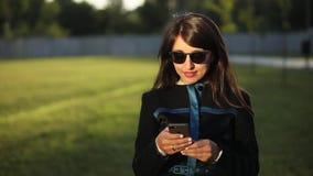 Donkerbruine jonge vrouwen in de slimme telefoon van het zonnebrilgebruik stock videobeelden