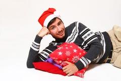 Donkerbruine kerel die met hoofdkussens liggen die de hoed van de Kerstman dragen Royalty-vrije Stock Afbeeldingen