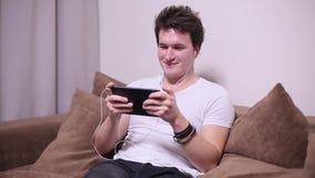 Donkerbruine kerel die op een video op de tablet letten stock videobeelden