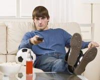 Donkerbruine kerel die op TV let Stock Foto