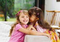 Donkerbruine kinderenzusters die gelukkig op wit zitten Stock Fotografie